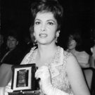 Gina Lollobrigida holding up award. - 8x10 photo