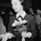 Audrey Hepburn holding flower bouquet. - 8x10 photo