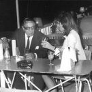 Jacqueline and Aristotle Onassis sitting at table drinking. - 8x10 photo