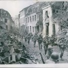 U.S. troops marching through a wrecked town. - 8x10 photo