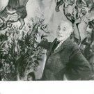 Marc Zakharovich Chagall standing in front of a painting. - 8x10 photo
