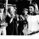Jacqueline Kennedy standing and carrying a glass bowl. - 8x10 photo