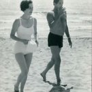 Robert Mitchum at beach with woman. - 8x10 photo