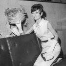Audrey Hepburn sitting on sofa. - 8x10 photo