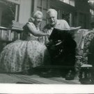 Ernest Hemingway looking at book, woman sitting aside.  - 8x10 photo