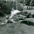 Eddy Merckx lying on chair in garden and pampering his dog.  - 8x10 photo