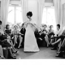 Claudia Cardinale in a white gown surrounded by people, in London. - 8x10 photo