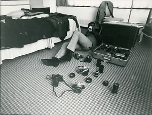 Sammy Davis Jr. lying on floor and taking photograph, many cameras and lenses on