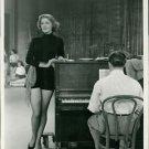 Arlene Dahl standing next to piano. - 8x10 photo