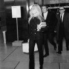 Brigitte Bardot smiling,carrying books, with Gunter Sachs. - 8x10 photo