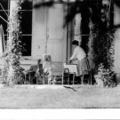 Charlie Chaplin sitting at outdoor table, with his wife Oona. - 8x10 photo