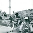 Hussein bin Talal with his wife standing inside the car, waving. - 8x10 photo