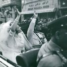 Hussein bin Talal with his wife sitting inside the car, waving.  - 8x10 photo