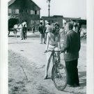 Irina Demich on cycle, talking to man.  - 8x10 photo
