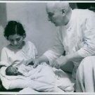 A man checking the newborn baby while the mother carrying it in Poland, 1939. -