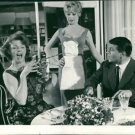 Brigitte Bardot with woman and man. woman is shouting at eating table.   - 8x10