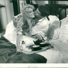 A man kissing Brigitte Bardot as she brings a tray of tea to bed in the morning.