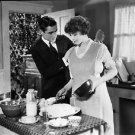 Man is assisting woman in kitchen.   people, man, woman, kitchen, assisting, c