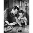 Close-up of a mature man with his son making a model of an airplane Canvas Art -  (24 x 36)