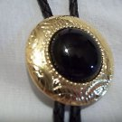 "Bolo Tie  Round Black Stone Goldtone Tips  and Holder 1 3/4"" Round Leather"