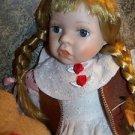 Blonde hair bangs braids blue eyed porcelain doll vintage Western style dress GC