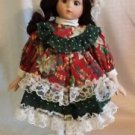 """12"""" porcelain doll green and red dress with white ruffled trim"""