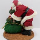 Santa Claus with Christmas bag of toys in front of fireplace Figurine