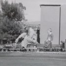 Black and White Photograph of a Man and a Baby Riding Small Scale Train Original