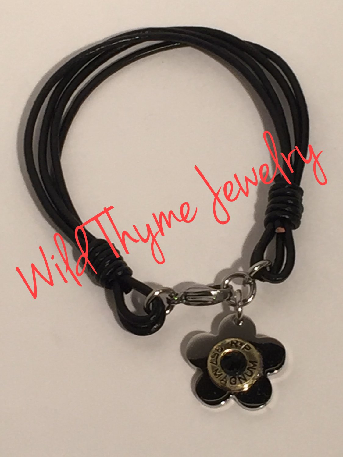 Leather bracelet with flower and bullet casing charm