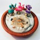 Miniature trio of fairy/gnome houses surrounding a realistic goldfish pond.