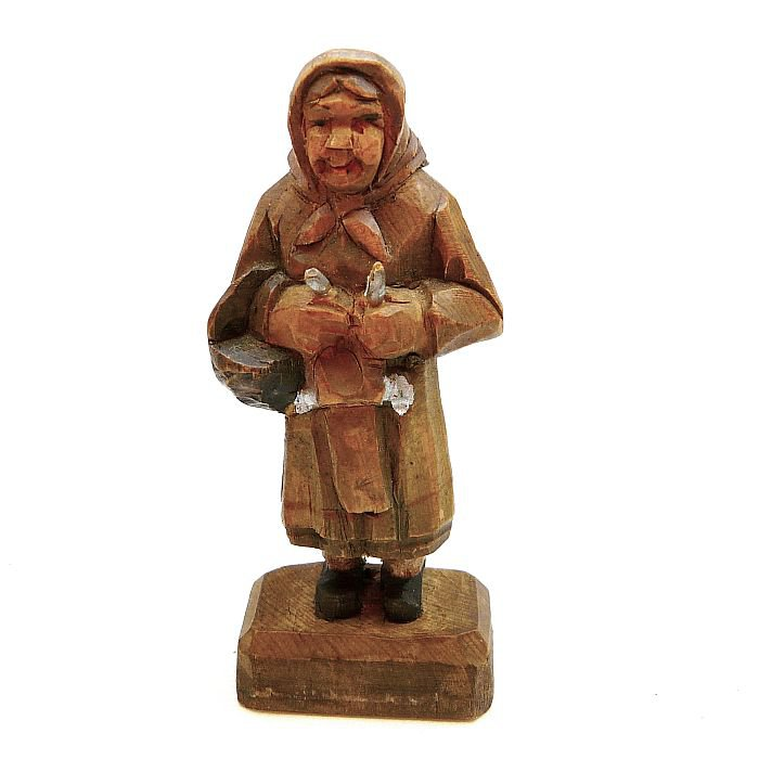 Vintage carved wood figurine of a woman knitting while standing