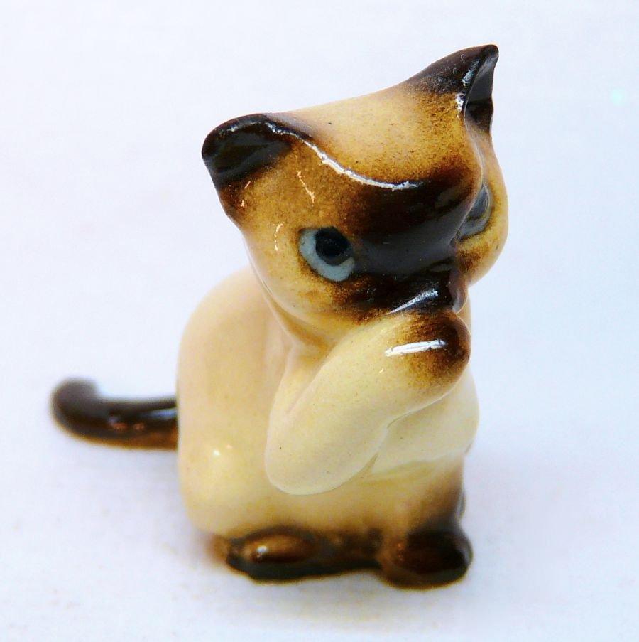 vintage miniature Siamese cat figurine washing its face