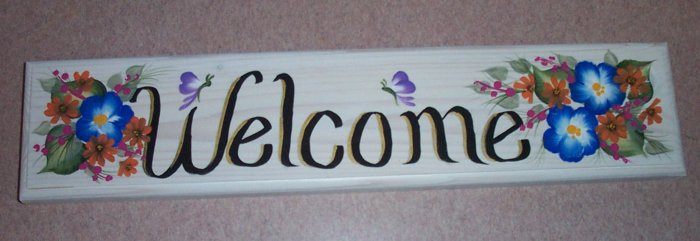 welcome sign with blue & small orange flowers