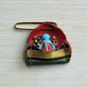 tiny blue celluloid doll pin with rhinestones in a leather pocket