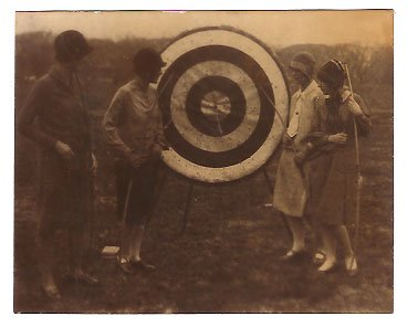 Real Photo of girls from the Marjorie Webster School examining archery target, 1926