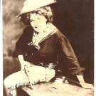 Real Photo of a woman in cowgirl outfit, holding revolver, seated on table, with playing cards, 1909