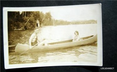 Early vintage photo man paddling an old canoe woman passanger