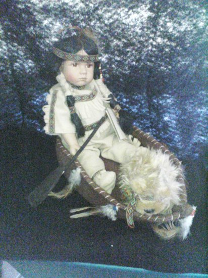 indian doll in a canoe