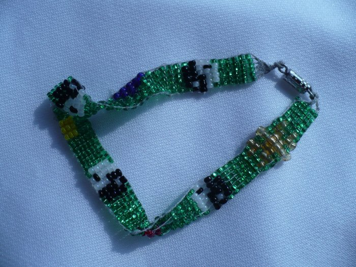 bracelet woven with glass seed beads background is green with 4 black and white yin -yang symbols