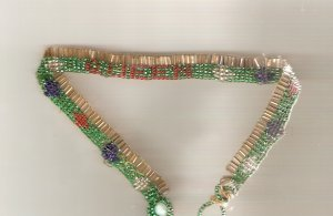 Gold red,blue and green choker spells out the word Queen