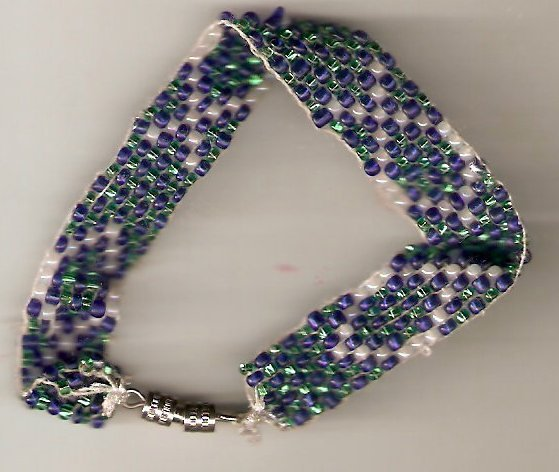 bracelet woven with blue green and white glass seed beads.  design is a simple white fish shape.