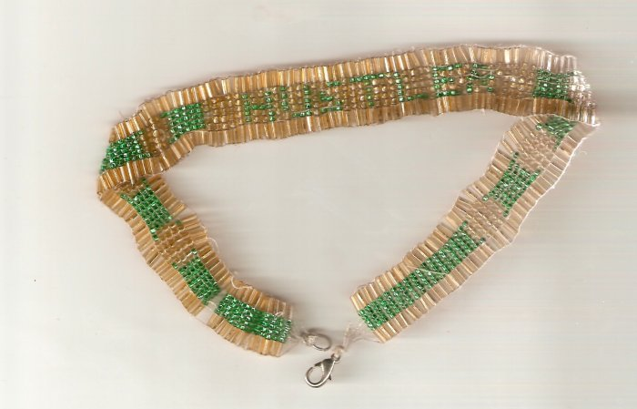 Necklace woven with green and gold seed beads and bugle beads spells out the word hustler