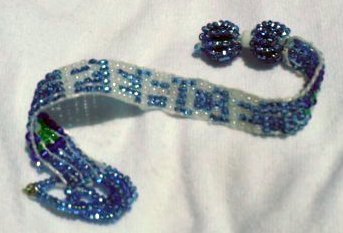 """blue  beaded bracelet spells out """"peace""""in white letters."""