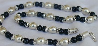 A silver necklace with onyx stones