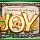 Christmas PIN #0062 JOY Signed GCI Goldtone with Orn, Star & Bell w/Green Holly