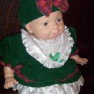 Holiday Hugs Goldberger Baby Doll wearing Green Velvet Christmas Dress and Bonnet