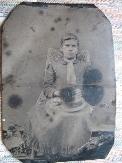 Small tintype portrait of young person seated