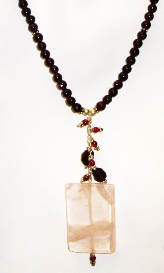 NK034       Rose Quartz Pendant in a Garnet Strand. Sterling Silver Beads and Clasps